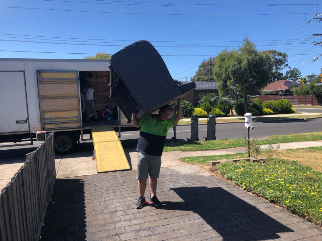 A fit removalist with outdoor setting on his shoulder